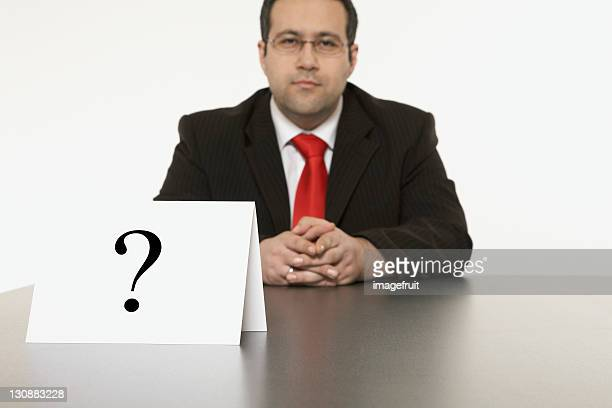 Businessman sitting at desk in front of a place card