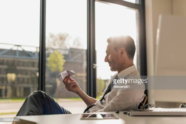 Businessman sitting at desk in his office looking at paper plane
