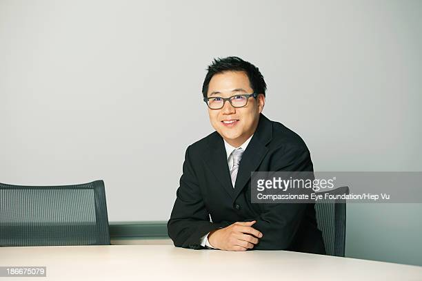 Businessman sitting at desk, looking at camera