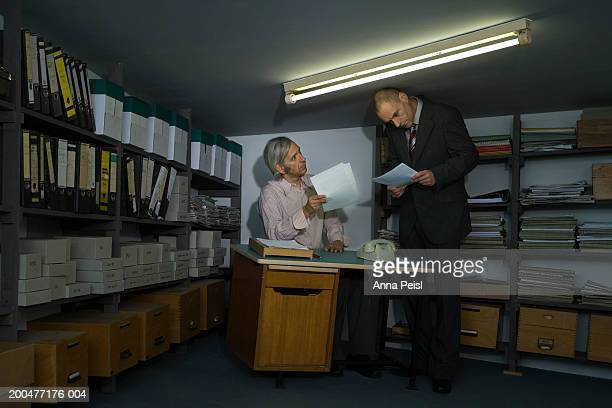 Businessman sitting at desk looking at documents with male colleague