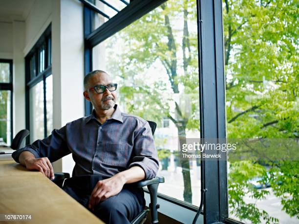 businessman sitting at desk looking out window - looking at view foto e immagini stock