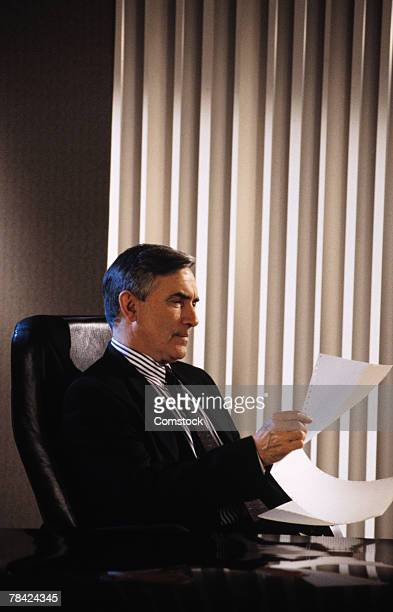 Businessman sitting at desk reading paperwork