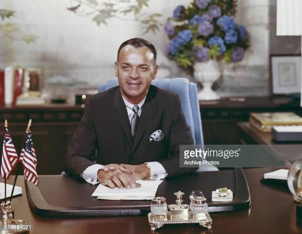 Businessman sitting at desk, smiling
