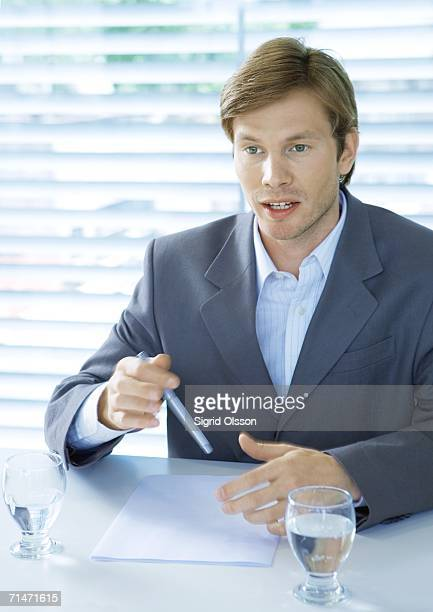 Businessman sitting at desk speaking and gesturing