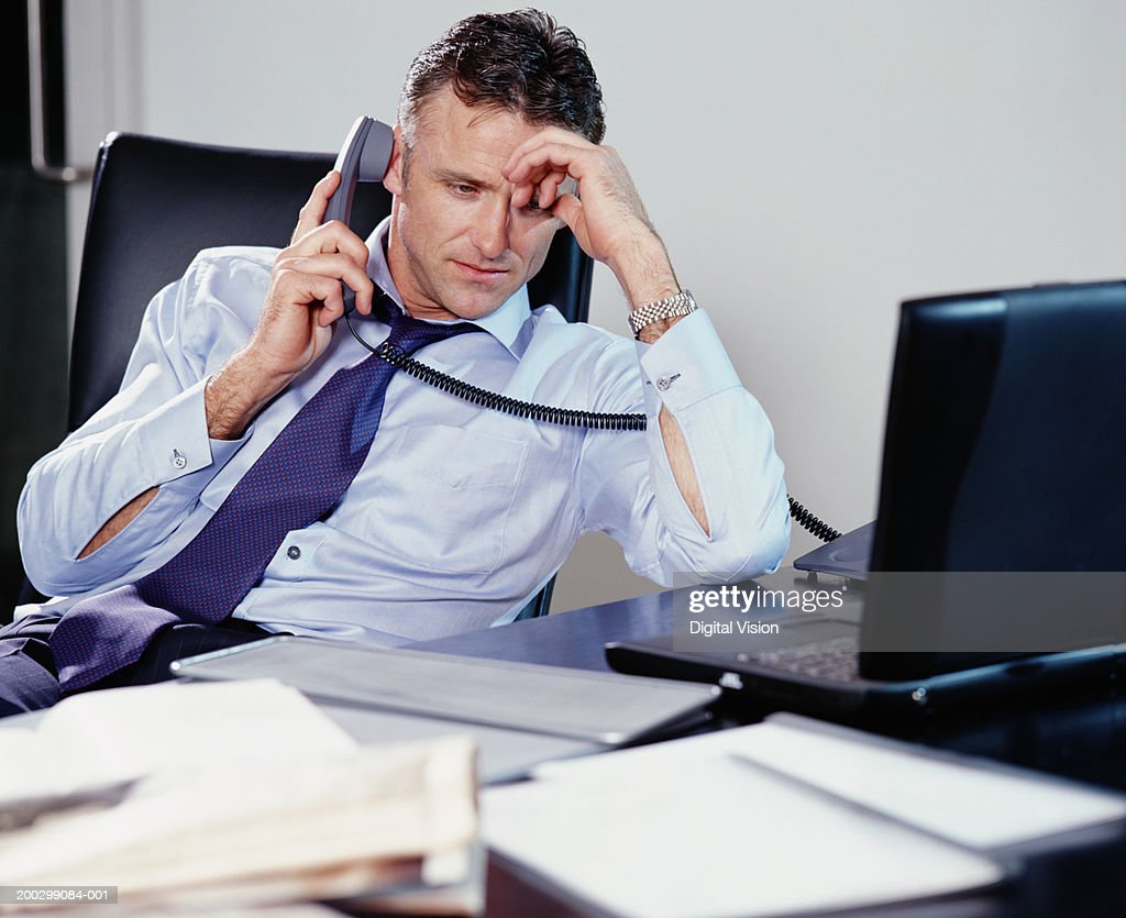 Businessman sitting at desk using phone, resting head on hand : Stock Photo
