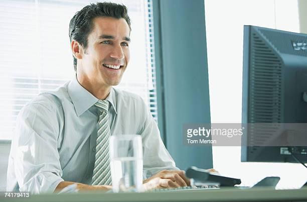 Homme d'affaires, assis au bureau avec ordinateur et souriant travail