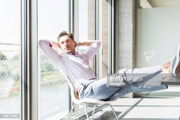 Businessman sitting at desk with feet up, looking out of window