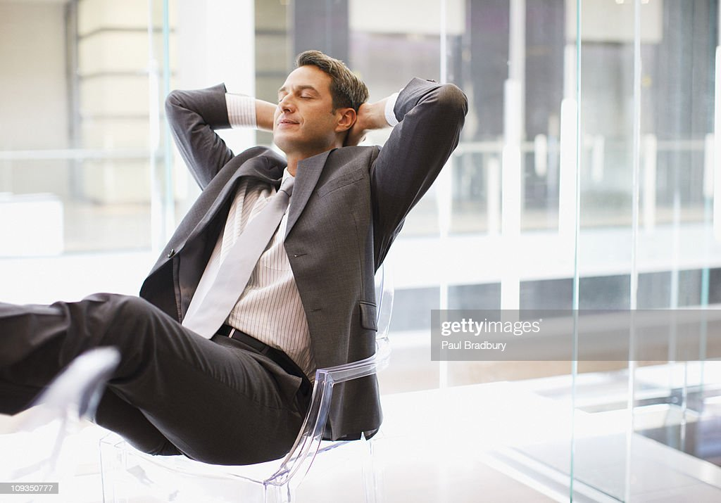 Businessman sitting at desk with feet up : Stock Photo