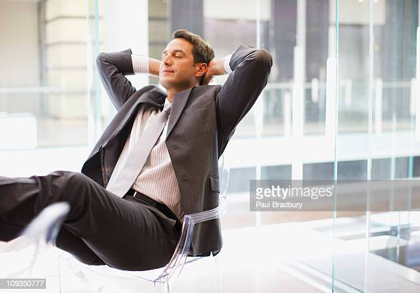 Businessman sitting at desk with feet up