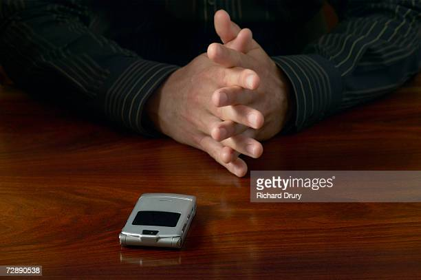 businessman sitting at desk with hands clasped, mobile phone on desk, close-up - richard drury stock pictures, royalty-free photos & images