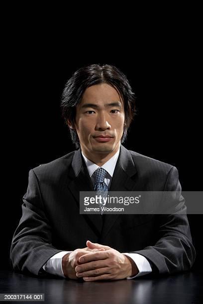 Businessman sitting at desk with hands together, portrait