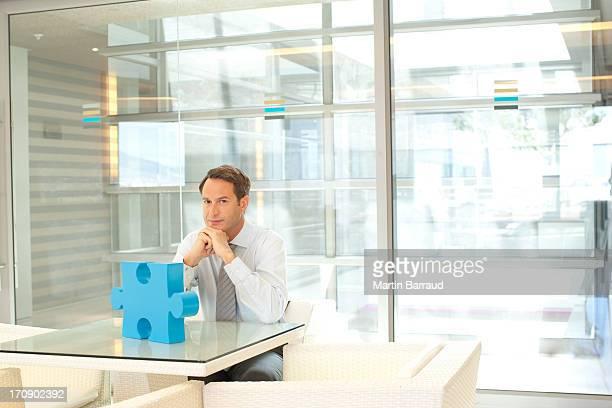 businessman sitting at desk with jigsaw puzzle piece - alleen één mid volwassen man stockfoto's en -beelden