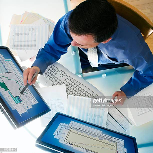 Businessman sitting at desk with two computer monitors.
