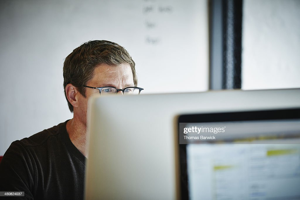 Businessman sitting at desk working on computer : Stock Photo