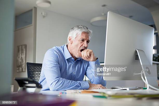 businessman sitting at desk, yawning - yawning stock pictures, royalty-free photos & images