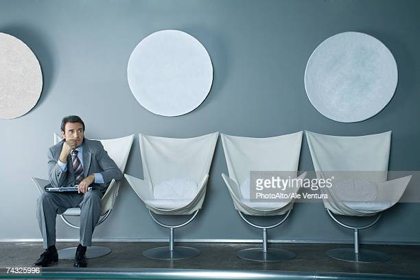 Businessman sitting at end of row of chairs, holding laptop on lap