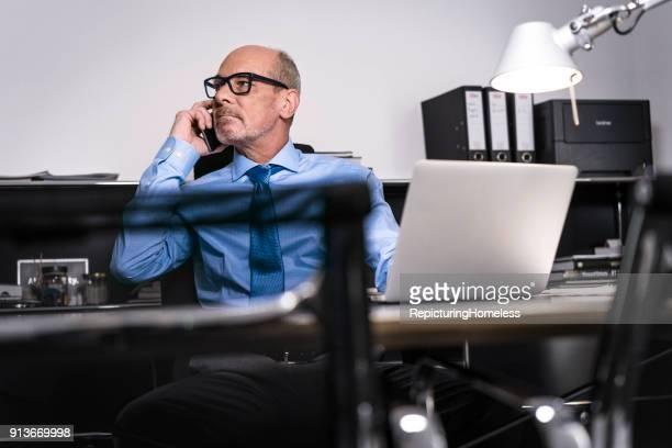 Ein Geschäftsmann telefoniert an seinem Schreibtisch und schaut nach Rechts