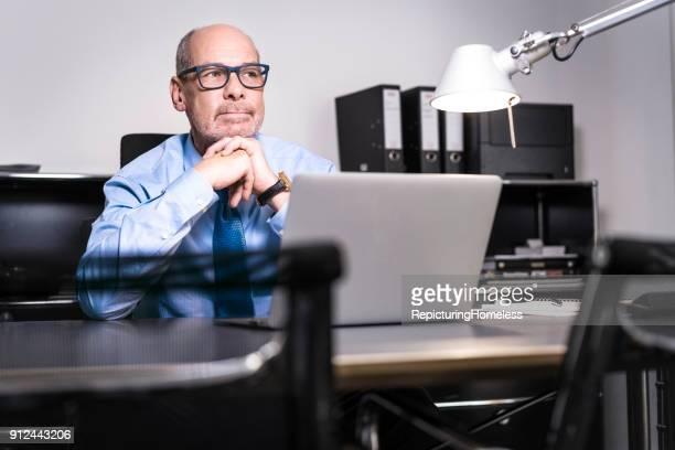 Ein Geschäftsmann mit verschränkten Fingern und schaut ins Leere