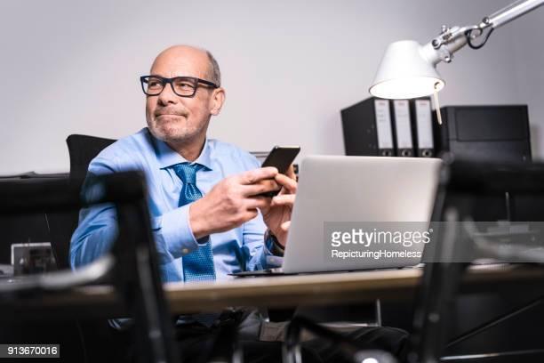 Ein Geschäftsmann hält sein Telefon in den Händen und schaut lächelnd nach Rechts