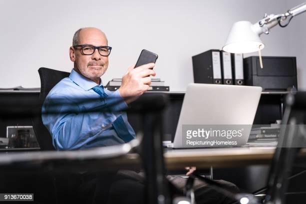Ein Geschäftsmann hält sein Telefon in der Hand und schaut in die Kamera