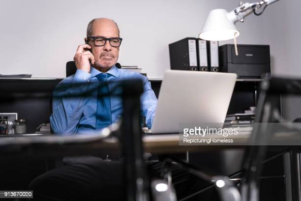 ein geschäftsmann telefoniert an seinem schreibtisch und schaut auf seinen laptop - repicturing homeless stock-fotos und bilder