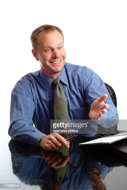 Businessman Sitting at his Desk Talking with a Client