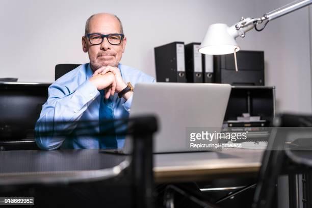 Ein Geschäftsmann mit verschränkten Händen schaut in die Kamera