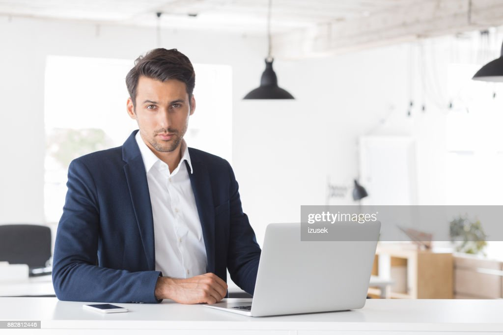 Businessman Sitting At His Desk With Laptop Stock Photo