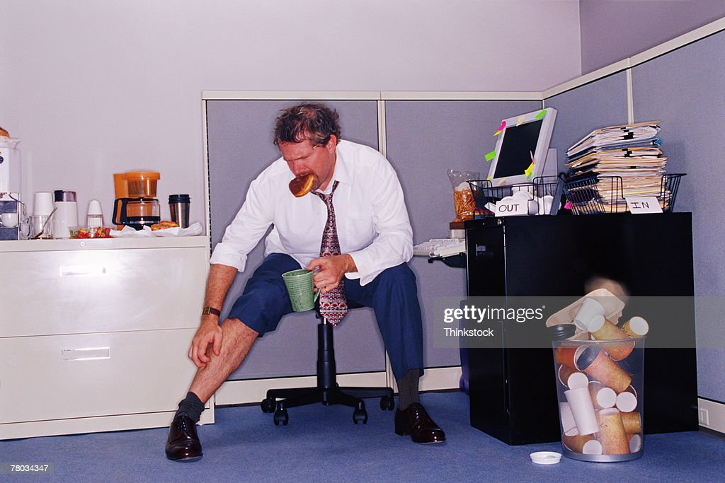 Businessman sitting at messy desk scratching his leg : Stock Photo