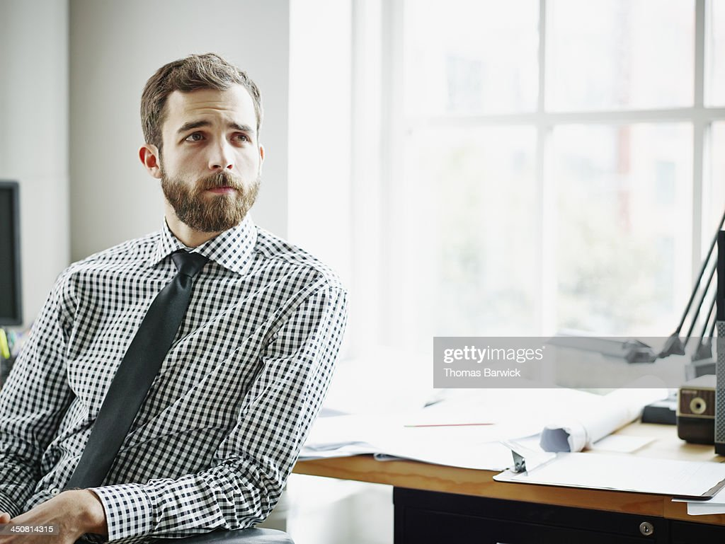 Businessman sitting at office workstation : Stock Photo