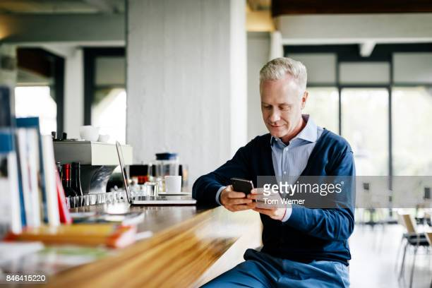Businessman Sitting At Restaurant Bar Using Smartphone