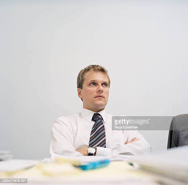 Businessman sitting at table, arms crossed