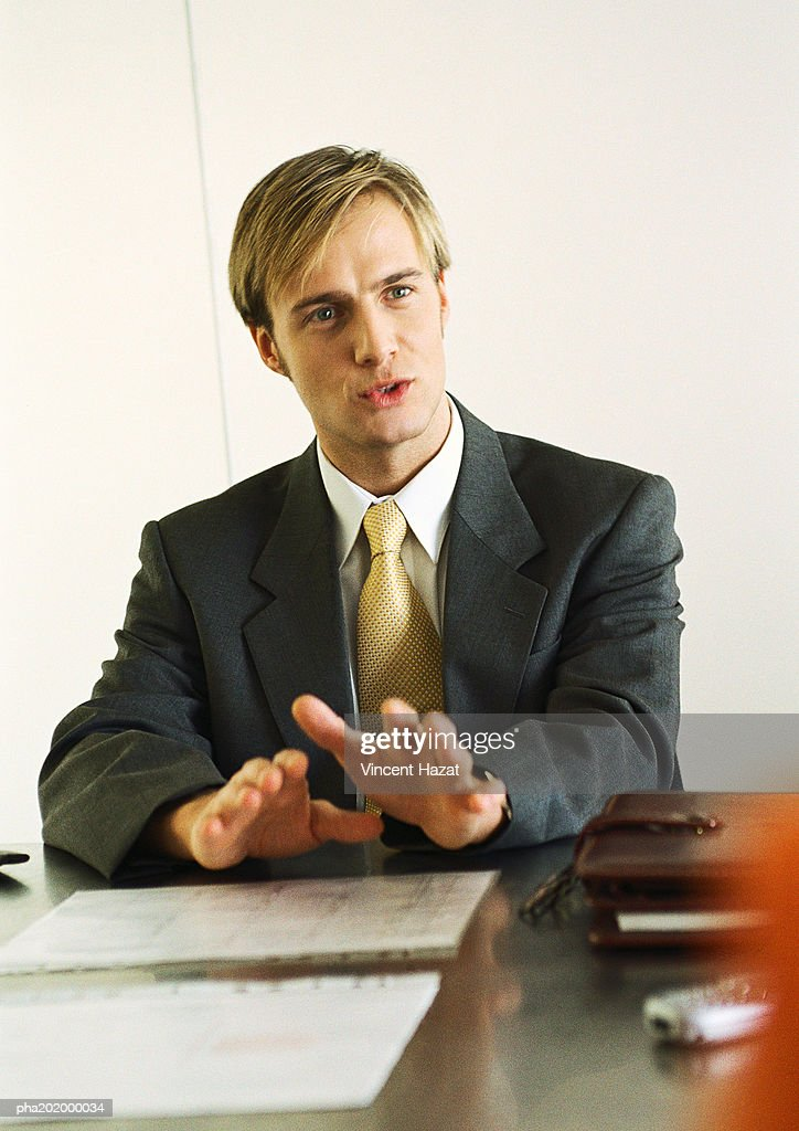 Businessman sitting at table talking. : Stockfoto