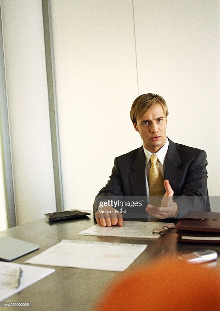 Businessman sitting at table talking. : Stockfoto