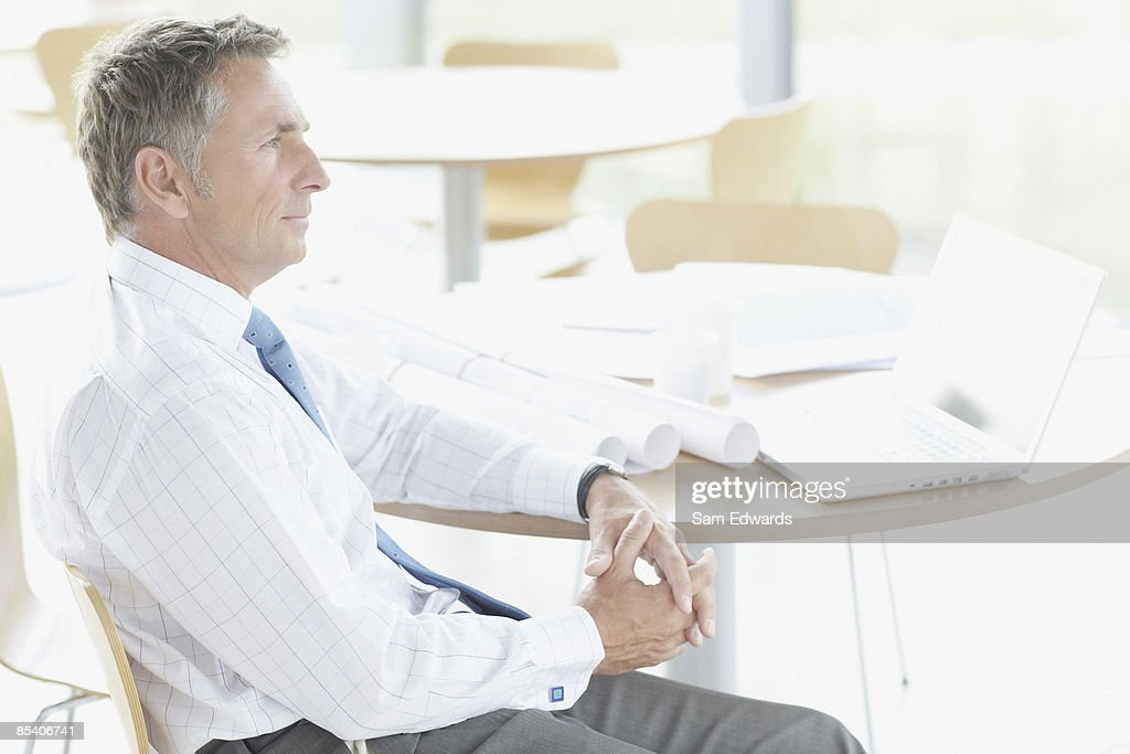 Businessman sitting at table with blueprints : Stock Photo