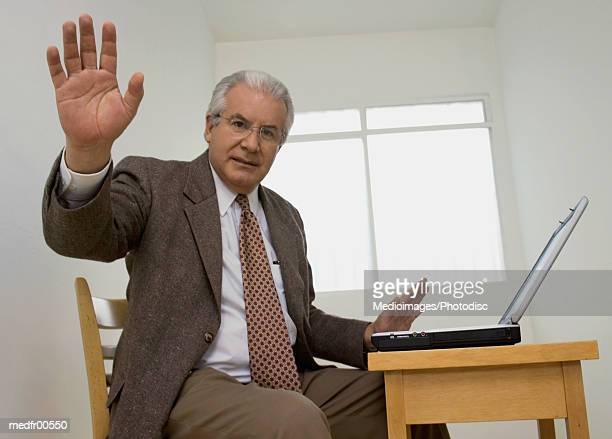 Businessman sitting at table with laptop and holding hand out in stop gesture