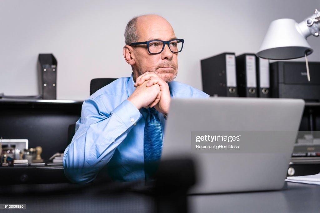 Ein Geschäftsmann sitzt mit verschränkten Händen an seinem Tisch : Stock-Foto