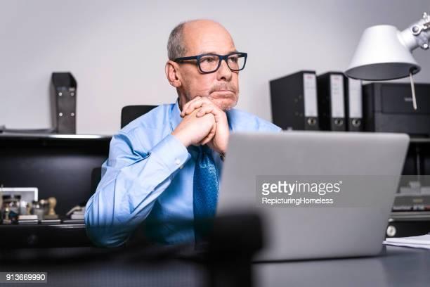 Ein Geschäftsmann sitzt mit verschränkten Händen an seinem Tisch