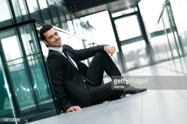 businessman sitting at the floor - gekanteld stockfoto's en -beelden
