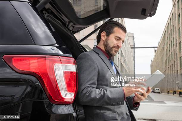Businessman sitting at the rear of his car