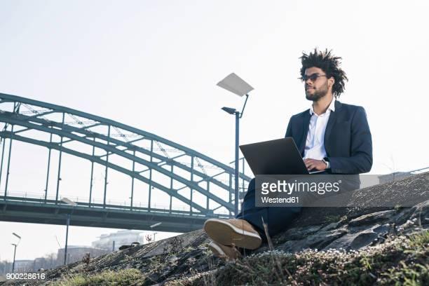businessman sitting at the riverside using laptop - 川岸 ストックフォトと画像