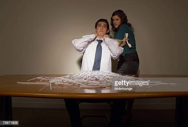 businessman sitting at untidy desk strangled by female colleague with telephone cord - women being strangled stock photos and pictures