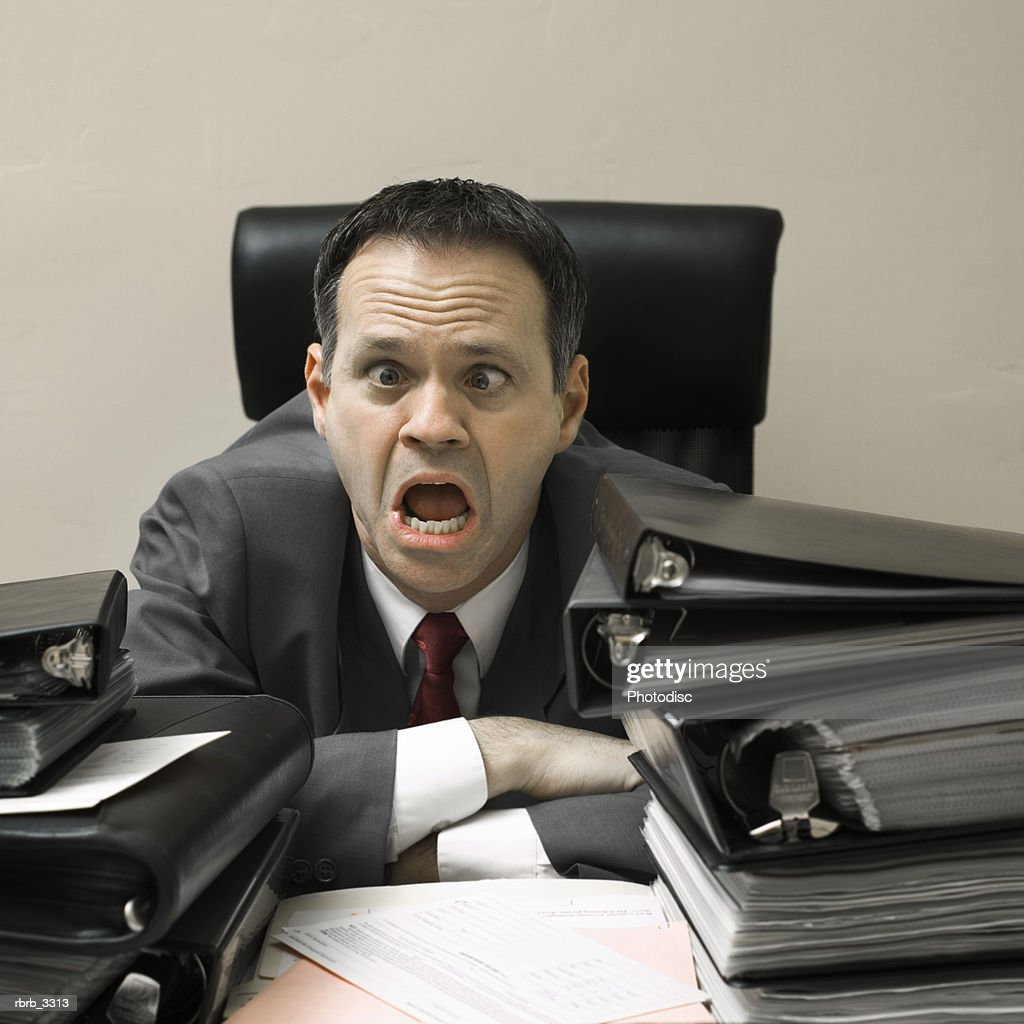 Businessman sitting behind a desk making a face : Stockfoto