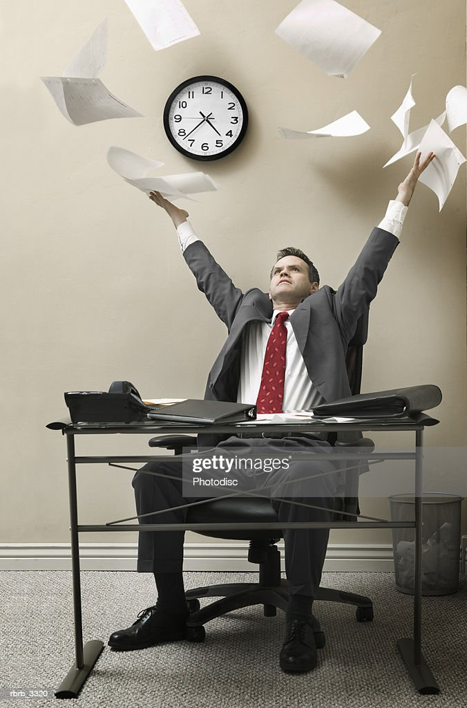 Businessman sitting behind a desk throwing sheets of paper in the air : Foto de stock