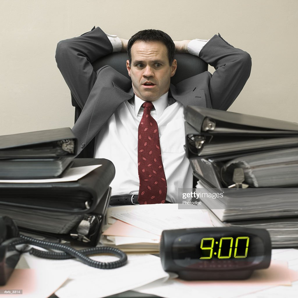 Businessman sitting behind a desk with his hands behind his head : Stockfoto