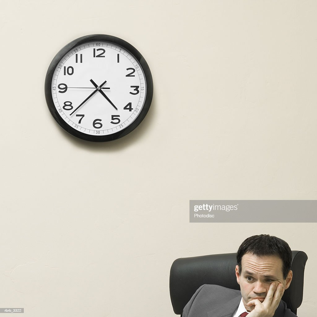 Businessman sitting behind a desk with his hands on his face : Stockfoto