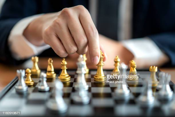 businessman sitting behind chess figure in competition success play. strategy, management or leadership concept - chess stock pictures, royalty-free photos & images