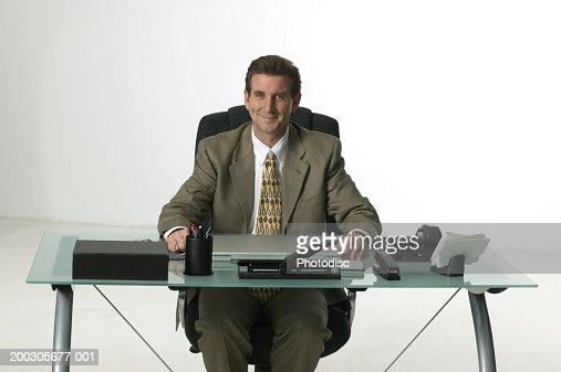 Businessman Sitting Behind Desk Posing In Studio Portrait Stock Photo Getty Images