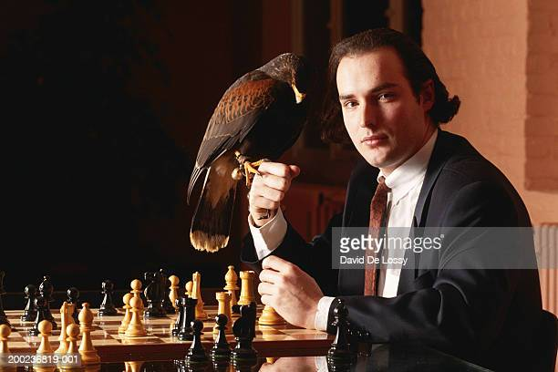 Businessman sitting by chessboard with bird on his fist