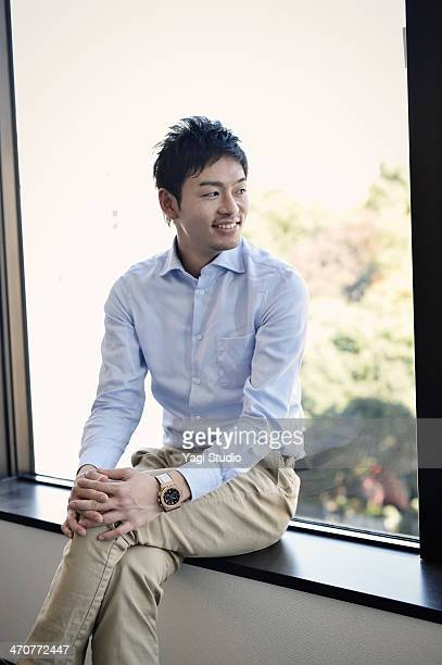 businessman sitting by the window of the office - 日本人のみ ストックフォトと画像